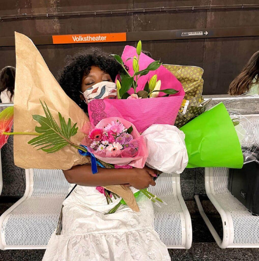 Christl Clear hält mehrere Blumensträuße, die sie bei ihrer Lesung im Volksgarten Pavillon bekommen hat während sie bei der Station Volkstheater auf die U-Bahn wartet