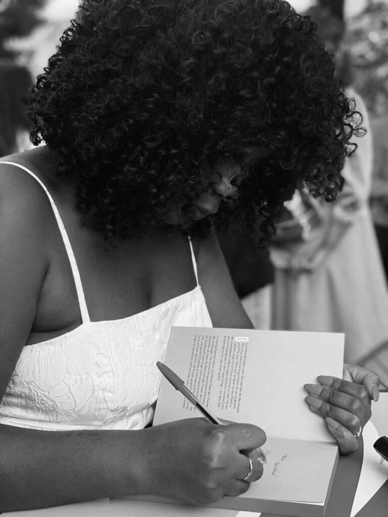 Christl Clear signiert ein Buch bei ihrer Lesung ihres ersten Buches Let me be Christl Clear im Volksgarten Pavillon