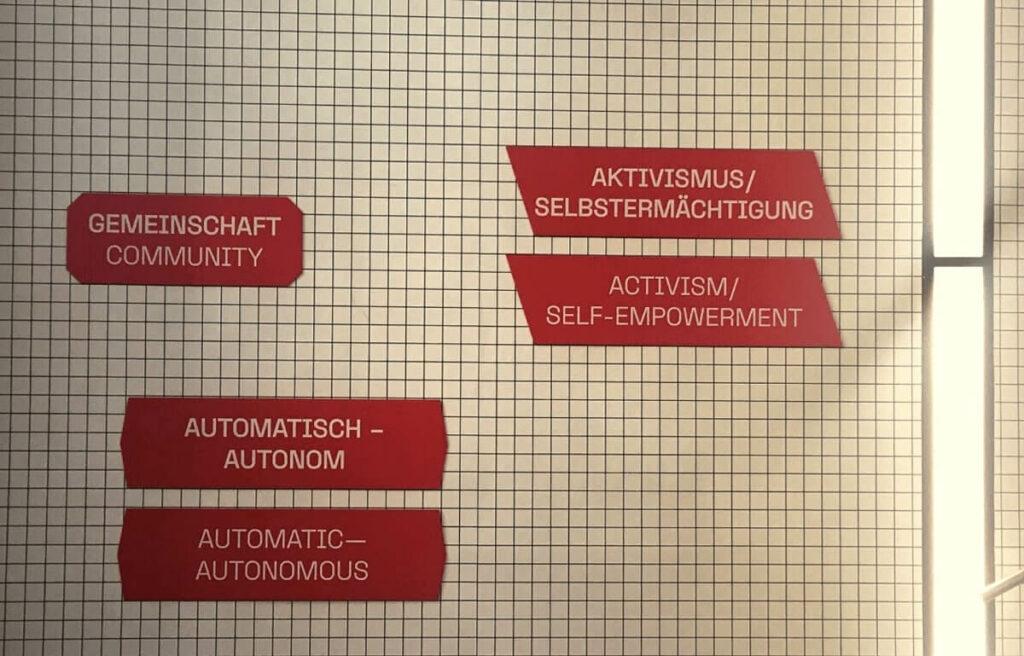 """Stiegenaufgang im MAK mit den Worten """"Gemeinschaft"""", """"Aktivismus/Selbstermächtigung"""" und """"Automatisch"""" in weißer Schrift auf rotem Hintergrund."""